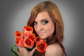Beautiful brown haired girl holding bouquet of flowers — Stockfoto