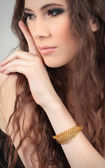 Cute girl touching her face with bracelet on her arm — Stock Photo