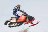 Flying sportsman on snowmobile — Stock Photo