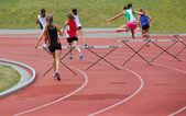 Girls running 200 meter hurdles — Stock Photo
