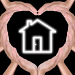 Royalty-Free Stock Photo: House icon in hands created heart