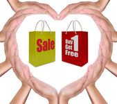 Sale label on shopping paper bag in hand heart — Stock Photo
