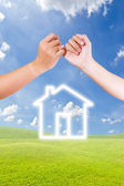 Hand linking finger and house icon — Stock Photo