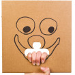Cardboard with sketch of smiling face in hand — Stock Photo