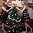 Two young beautiful girls decorate christmas tree — Stock Photo