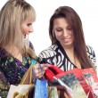 Two stunning girls looking in shopping bads — Stock Photo