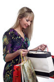 Beautiful young girl looking in shopping bags — Stock Photo