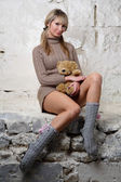 Sexy girl with teddy bear sitting on wall — Stock Photo