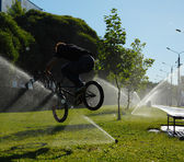 Boy jumping over fountain on bmx — Stock Photo