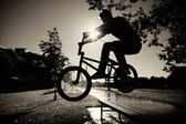Boy jumping over bench on bmx — Stok fotoğraf