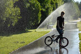 Boy with bmx stay on fountain splashes background — Stock Photo