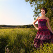 Beautiful girl in dress on field - Stock Photo