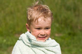 A boy of four years, wrapped in a towel after bathing in the riv — Stock Photo