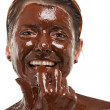 Young woman having a chocolate face mask - Stock Photo