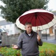 Mature male holding an umbrella — Stock Photo