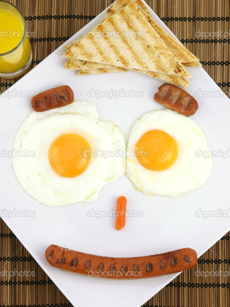 Breakfast on a plate of a funny face made from fried eggs, sausages and toast   Stock Photo #5531105
