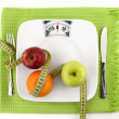 Diet concept. Fruits with measuring tape  on a plate like weight scale — Zdjęcie stockowe