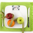 Diet concept. Fruits with measuring tape on a plate like weight scale — Foto de Stock