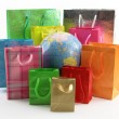 Shopping bags around of the world globe — Stock Photo