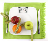 Diet concept. Fruits with measuring tape on a plate like weight scale — Stock Photo