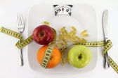 Fruits and vitamins with measuring tape on a plate like weight scale — Stock Photo