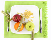 Fruits and vitamins with measuring tape on a plate — Стоковое фото