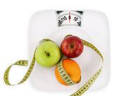 Diet concept. Fruits with measuring tape on a plate like weight — Stock Photo
