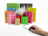 Computer mouse connected to a group of shopping bags with a globe inside — Stock Photo