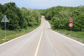 Winding country road with speed limit sign — Stock Photo
