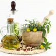 Stock Photo: Mortar and pestle with herbs and bottles of olive oil