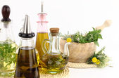 Mortar and pestle with herbs and bottles of olive oil — Stock Photo