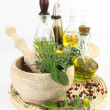 Mortar and pestle with herbs and bottles of olive oil — Stock Photo #5973922