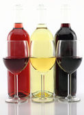 Three colors of wine in bottles and glasses — Stock Photo