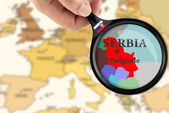 Magnifying glass over a map of Serbia — 图库照片