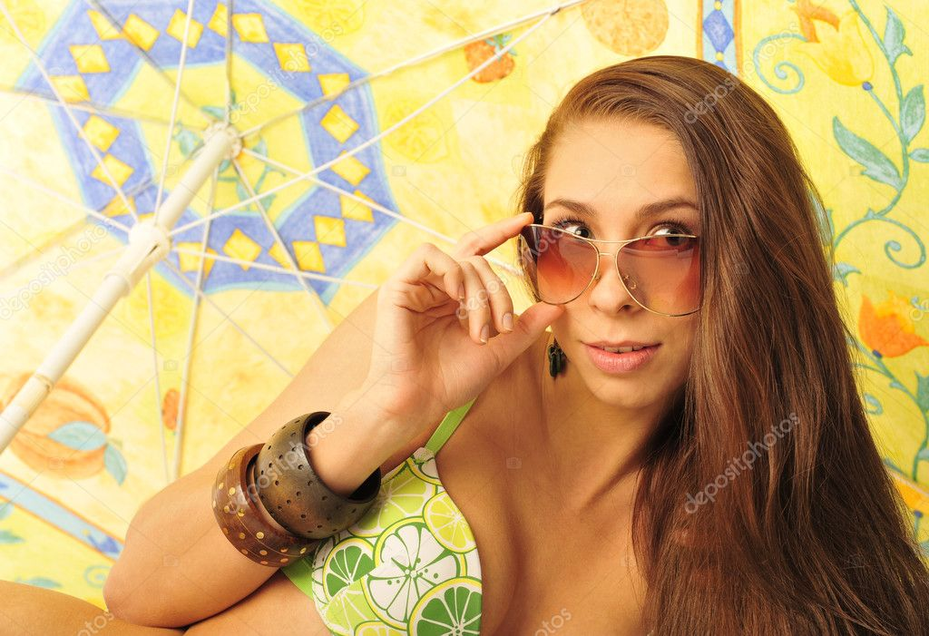 A young and sexy lady in swimsuit and sunglasses under umbrella on a hot day  Stock Photo #5420375