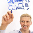 Young man with a plan of a house - Stock Photo