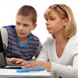 Stock Photo: Portrait of adult woman watching as her son doing homework