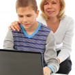 Portrait of adult woman watching as her son doing homework — Stock Photo
