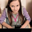 Young girl doing her work on laptop sitting on an armchair — Stock Photo