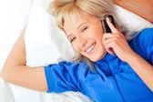 Mooie jonge blonde vrouw op het bed thuis — Stockfoto