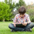Stock Photo: Young boy outdoors on the grass at backyard
