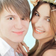 Smiling young man embracing his pretty girlfriend wearing hay ha — Stock Photo #5756758