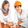 Portrait of two young women discussing construction project. — Stock Photo
