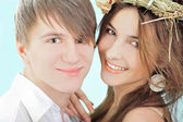 Smiling young man embracing his pretty girlfriend wearing hay ha — Stock Photo