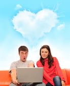 Portrait of a young couple using a computer — Stock Photo