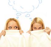 Dwie kobiety, szepcząc i niesamowite pod koc — Zdjęcie stockowe