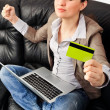 Stock Photo: Portrait of a young woman lying on the couch and shopping from t