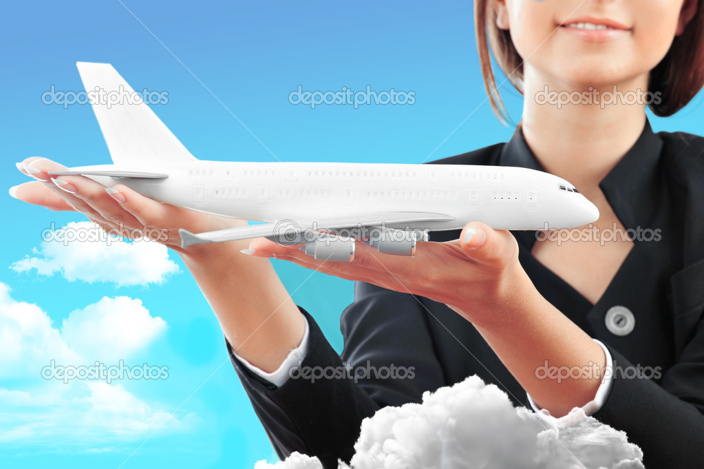Portrait of young happy woman stewardess holding jet aircraft in her arms on foreground. Advertisement banner for transport companies — Photo #5866618