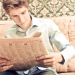 Closeup portrait of young man with newspaper - Lizenzfreies Foto