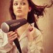 Beautiful woman drying her hair with hairdryer - Stock Photo